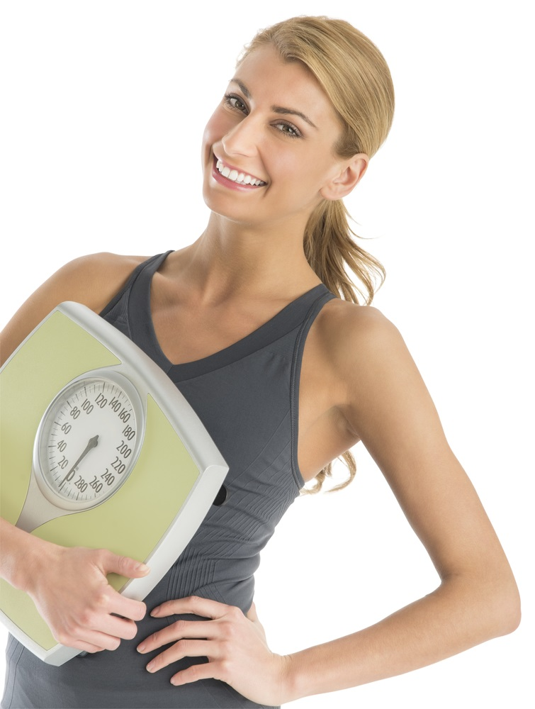 Happy Woman In Sports Clothing Holding Weight Scale