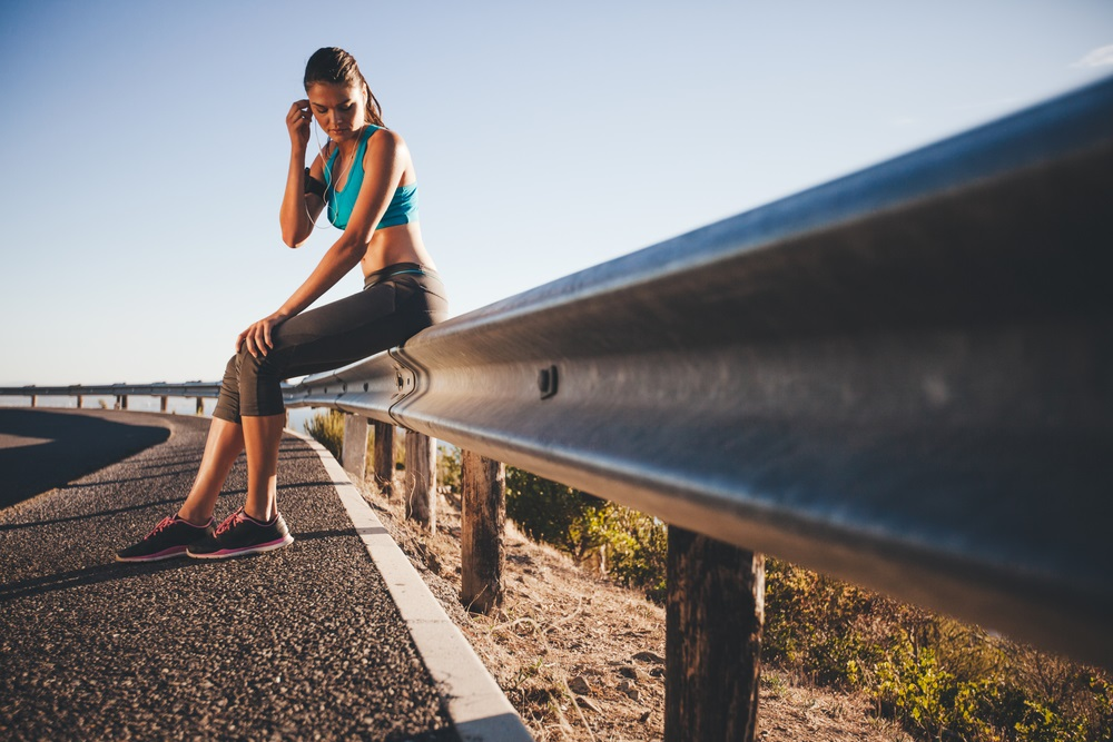 Young athlete taking break from running workout