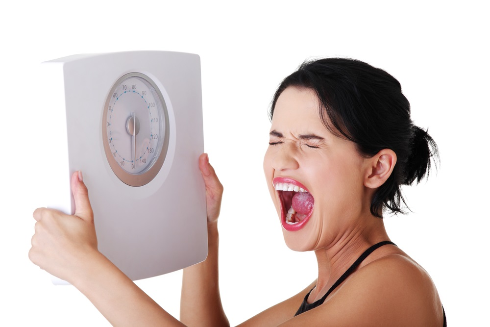 Frustrated woman with scale