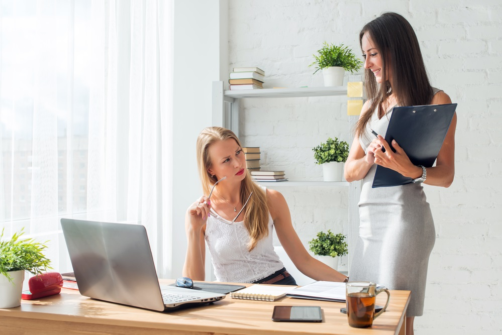 Two young woman colleague at office working standing and talking.